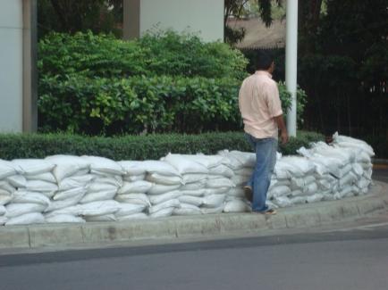 Karung-karung yang ditumpuk menjadi bendung penghalang banjir masuk gedung di Bangkok